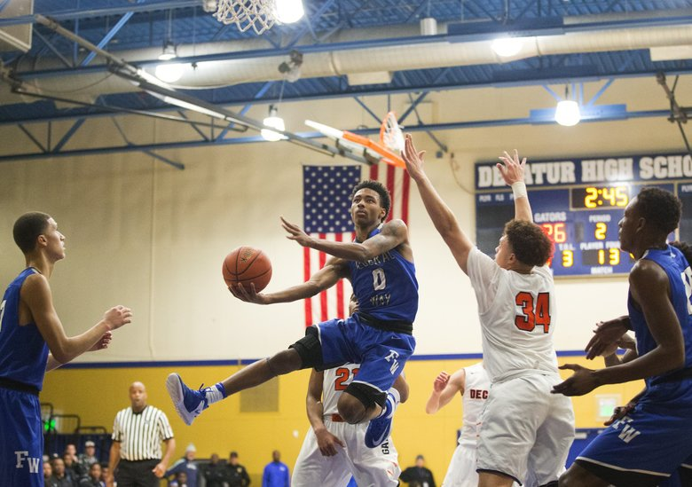 Federal Way point guard Marcus Stephens lobs the ball at the basket, flanked by fellow seniors Rashon Slaughter, left, and Malcolm Cola at Decatur.  (Lindsey Wasson/The Seattle Times)