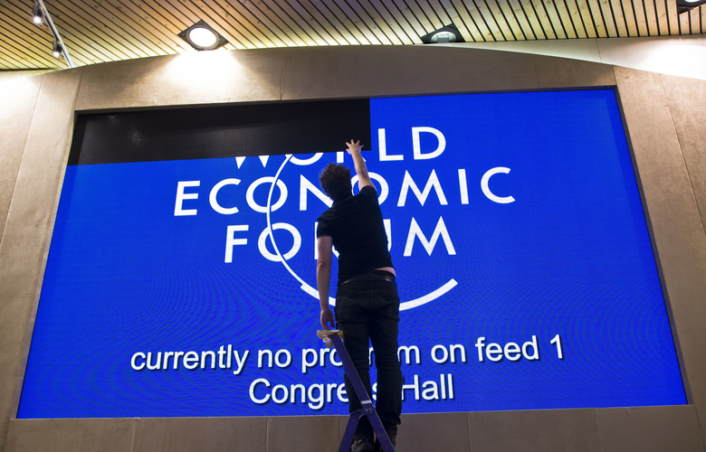 A staff member adjusts a giant screen at the congress center where the annual meeting, World Economic Forum, will take place in Davos, Switzerland, Sunday Jan. (AP Photo/Michel Euler)