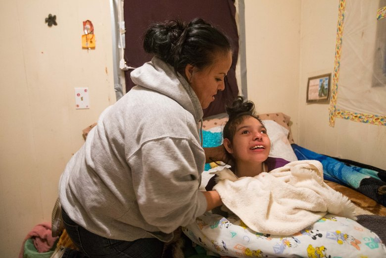 Resident Olga Zambrano helps her special-needs daughter, Aymy, 14, at their home in the Shady Brook park.  (Sofia Jaramillo/Yakima Herald-Republic)