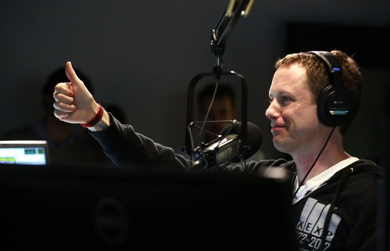 KEXP DJ John Richards gives a thumbs-up during the first broadcast in the radio station's new studios at the Seattle Center on Wednesday, Dec. 9, 2015. (Erika Schultz/The Seattle Times)