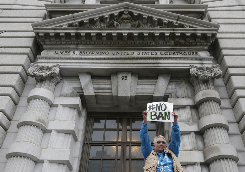 FILE – In this Feb. 7, 2017, file photo, Karen Shore holds up a sign outside of the 9th U.S. Circuit Court of Appeals in San Francisco, Calif. President Donald Trump's administration said in court documents on Thursday, Feb. 16, 2017, it wants an end to the legal fight over its ban on travelers from seven predominantly Muslim nations and will instead issue a replacement ban.  (AP Photo/Jeff Chiu, File)