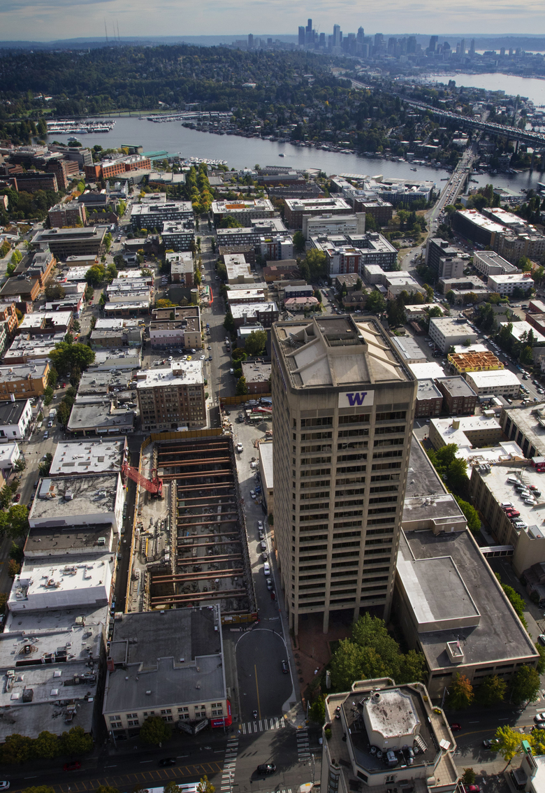 Aerial photo of the U District station location, the hole to the left of the high-rise, looking south. The station is near Northeast 43rd Street and Brooklyn Avenue East. The city is considering a proposal to upzone the neighborhood to accommodate larger buildings, similar to the UW office tower planned for above the station.  (Ellen M. Banner/The Seattle Times)