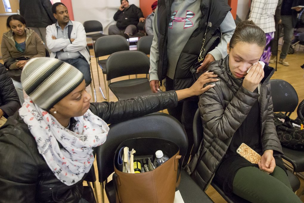 Aisha King, left, comforts Celestine Bolton as she becomes upset talking about the housing crisis. (Bettina Hansen/The Seattle Times)