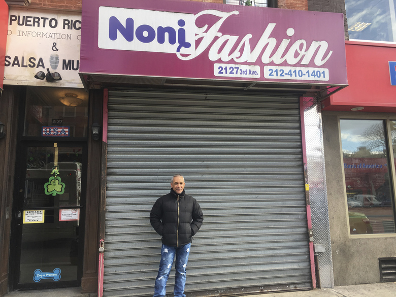 """Custo Diaz poses in front of his closed shop, Noni Fashion, a women's clothing store at 116th Street in the East Harlem neighborhood of New York, on Thursday Feb. 16, 2017. He was participating in the boycott called A Day Without Immigrants, aimed squarely at President Donald Trump's efforts to crack down on immigration. Diaz, a Dominican immigrant, said he closed his shop in support of all the immigrants who are """"feeling attacked"""" these days. Diaz said he has lived for 40 years in the U.S. and he stands in solidarity with his """"undocumented brothers and sisters."""" (AP Photo/Claudia Torrens)"""