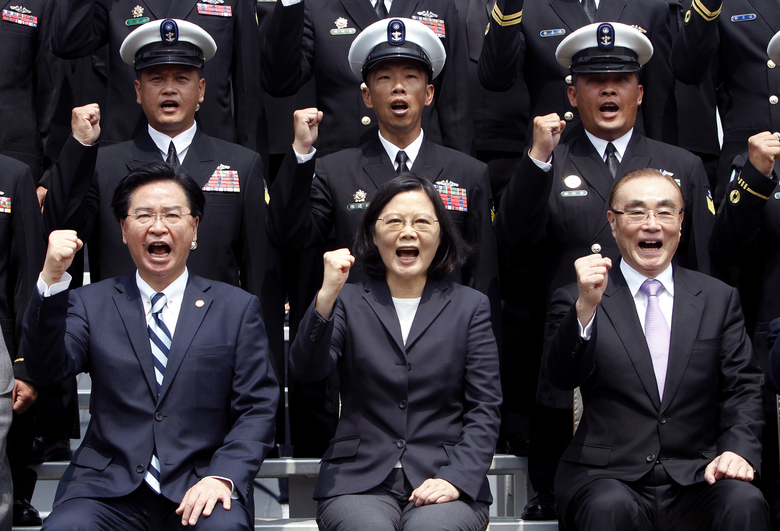 Taiwan's President Tsai Ing-wen, center, along with Defense Minister Feng Shihkuan, right, and Secretary-General of National Security Council Joseph Wu, cheers with soldiers during a visit to Zuoying naval base in Kaohsiung, southern Taiwan, Tuesday, March 21, 2017.  Tsai talks about the plan of manufacturing submarines domestically in a bid to enhance Taiwan's defense capabilities.(AP Photo/ Chiang Ying-ying)