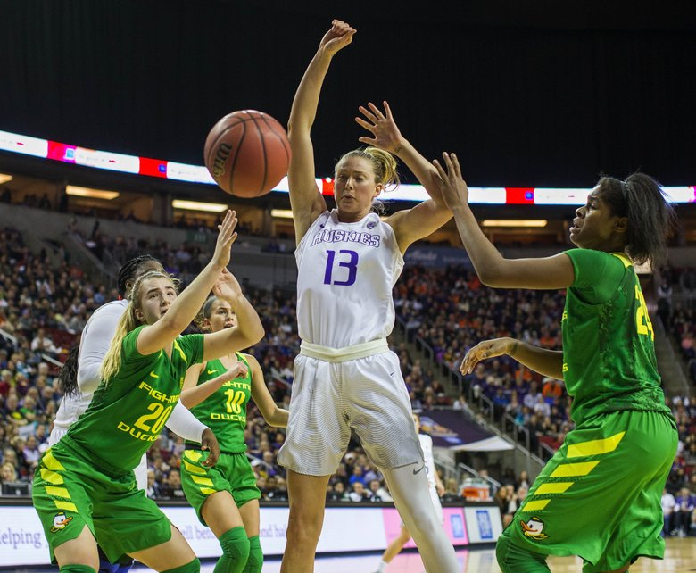 Washington's Katie Collier is fouled by Oregon's Ruthy Hebard, right, as she goes up for a shot in the lane late in the 2nd quarter. (Dean Rutz/The Seattle Times)