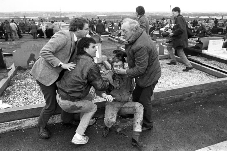 FILE – In this March 16, 1988 file photo an injured man is aided by mourners, including Sinn Fein vice president Martin McGuinness, left, at Milltown Cemetary, Belfast, after a gun and bomb attack killed three and left four seriously injured, at the funerals of three IRA members killed in Gibraltar. McGuinness, the Irish Republican Army commander who led his underground, paramilitary movement toward reconciliation with Britain, and was Northern Ireland's deputy first minister for a decade in a power-sharing government, has died, his Sinn Fein party announced Tuesday, March 21, 2017,  on Twitter. He was 66. (David Jones PA via AP)