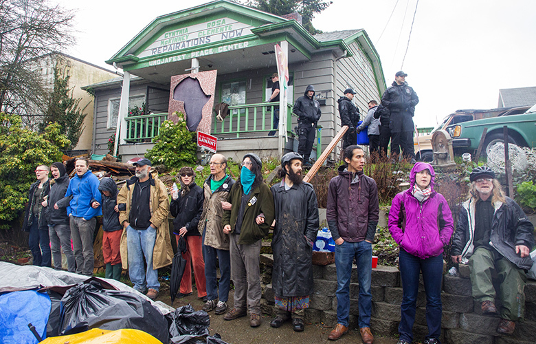 Seattle Police and law enforcement shows up to evict activist Omari Tahir Garrett from this house on East Spring Street between 23rd and 24th Avenues.