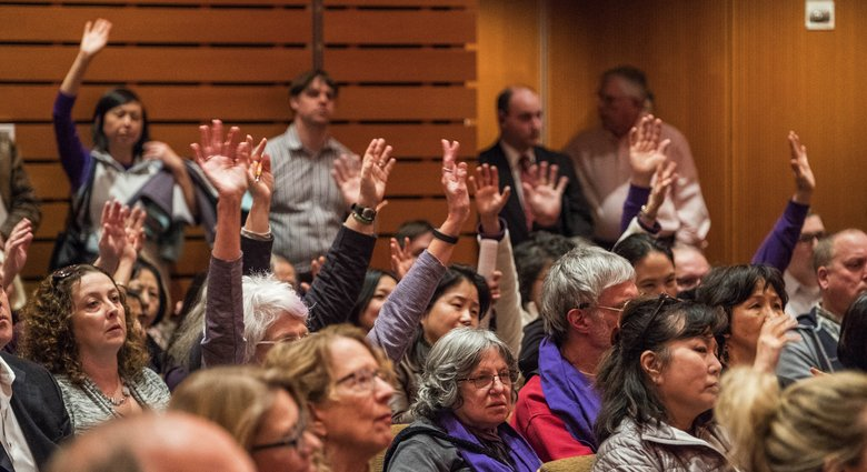 During public testimony during a Bellevue City Council meeting Monday about a controversial proposal to build a permanent men's homeless shelter in the Eastgate neighborhood, members of the audience raised and waived their hands to express agreement with speakers. (Dean Rutz/The Seattle Times)