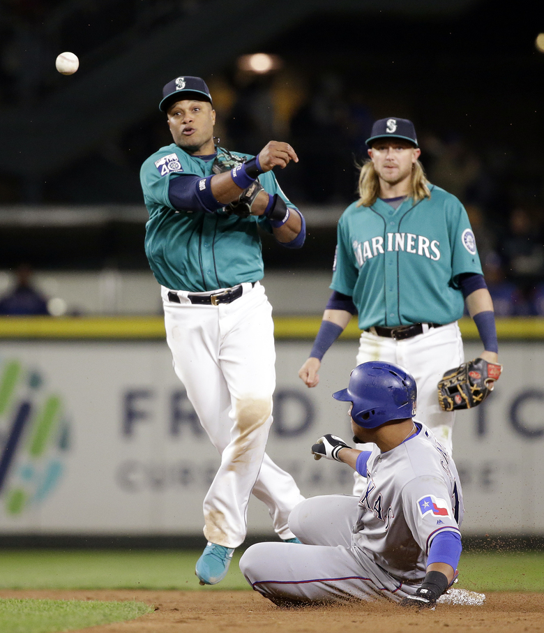 Seattle Mariners second baseman Robinson Cano, left, throws to first after forcing out Texas Rangers' Carlos Gomez at second base in the sixth inning of a baseball game Friday, April 14, 2017, in Seattle. Mariners shortstop Taylor Motter is at rear. Shin-Soo Choo was out at first. (AP Photo/Elaine Thompson) — WAET110 (Elaine Thompson/AP)