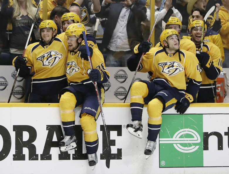 Nashville Predators players jump onto the ice to celebrate after defeating the Chicago Blackhawks 4-1  in Game 4 of a first-round NHL hockey playoff series Thursday, April 20, 2017, in Nashville, Tenn. The Predators swept the series. (AP Photo/Mark Humphrey)