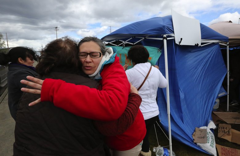Maru Mora Villalpando, left, organizer of the encampment outside the Northwest Detention Center in Tacoma, hugs a supporter. (Alan Berner/The Seattle Times)