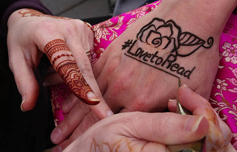 """Sarah Walters applies """"Love to Read"""" in henna to Brenda Spoonemore director of Kindle books at Amazon's celebration of World Book Day."""