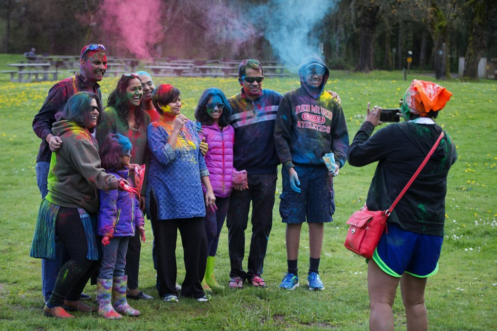 After throwing dry powder on each other, a group gathers for a photo taken by Leena Ghosh of Bellevue, right, at Vibha's Holi held at Lake Sammamish State Park in Issaquah on Saturday.  (Ellen M. Banner/The Seattle Times)