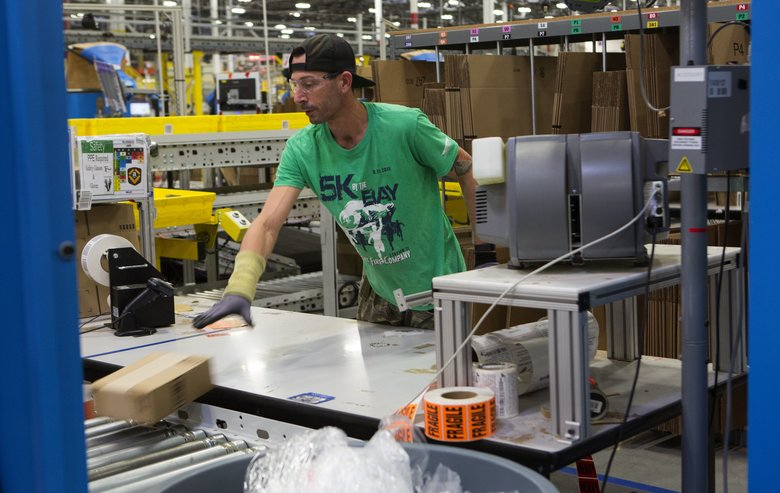 A worker handles a package at Amazon's fulfillment center in DuPont. The online retailer plans to hire 25,000 part-time jobs in fulfillment centers in the next year. (Ellen M. Banner/The Seattle Times)