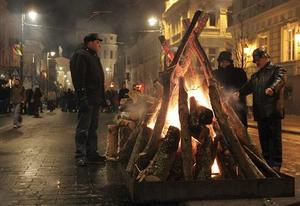 Lithuanians warm up by a fire during the celebration of independence day on Gediminas Avenue in Vilnius today.