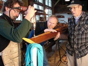 Steve Chapin drills a drain hole in the bow of a new Pocock cedar single as his assistant, Jim Kellogg, steadies the boat and Bob Brunswick looks on. Brunswick was an employee of Pocock Racing Shells Inc. for 54 years.