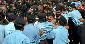 Pakistani lawyers jostle to enter in the Supreme Court during an anti government rally in Islamabad, Pakistan on Thursday. Supporters of Pakistan's suspended chief justice Iftikhar Mohammed Chaudhry showered him with rose petals at a hearing on his dismissal, hen clashed with police who stopped them from following the judge into the Supreme Court. Protesters chanted slogans in favor of Chaudhry on his case hearing.