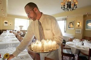 Waiter Mike Albritton sets out candles before the start of a wine dinner at Campagne restaurant.