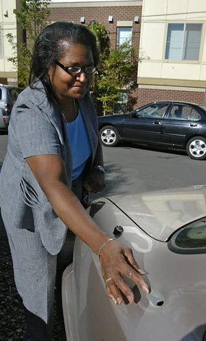 Ernestine White looks at a bullet hole in her car before heading to work Tuesday. The hole was the result of a shooting in South Seattle in which three people were injured, one of them fatally.