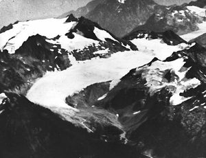 The South Cascade Glacier, seen here in 1928, has been measured annually since 1959 and is one of three West Coast glaciers used as indicators of what is happening to Western glaciers. The large mountain flanking its eastern side (to the left) is 8,261-foot Sentinel Peak. The glacier sits roughly six miles south of North Cascades National Park, east of Darrington. In 1928, the glacier was approximately 5 kilometers (3 miles) long. The next two photos will show how the glacier has changed over the years.