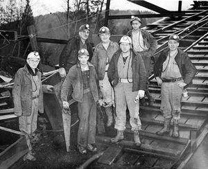 A committee of miners stand at the entrance of the Landsburg Mine near Ravensdale in January 1954 after deciding it was too dangerous to continue the search for trapped miner Harry English. The 40-year-old miner was buried under tons of coal and rock in a cave-in 400 feet underground. At left is Clarence Holmes, state mining inspector, who announced the decision. The Landsburg mine operated from about 1937 until 1960, when it was replaced by the Rogers mine.