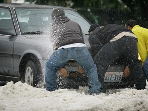 Three friends help another get his car unstuck Tuesday in White Center. After a few minutes, they were on their way. Not everyone in the Puget Sound region found it that easy.