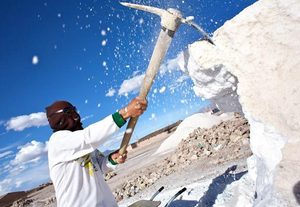 A worker chips salt from the Salar de Uyuni (Uyuni Salt Flats) in Bolivia, home to the world's largest lithium reserves. Bolivians are debating how to best take advantage of the resource.