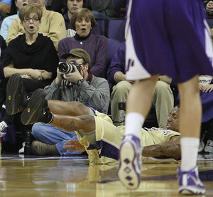 Fans react with shock as Washington's Isaiah Thomas goes flying after being hit during a game against Portland Saturday, Dec. 19, 2009, in Seattle. Despite hitting the hardwoods, a foul was called on Thomas.