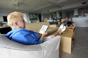 Wilma Sanders reads on her Kindle, on Marco Island, Fla., with her friend, Harold Roth. Within a few months, the prices for digital books will be $12.99 to $14.99.