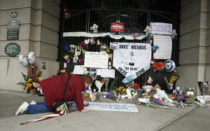 Karen Liesse of Kent adds a remembrance to the tribute outside the home plate gate at Safeco Field Saturday.