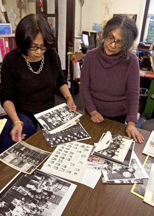Marya Castillano Bergstrom, left, and Dorothy Laigo Cordova, sisters who grew up attending Immaculate Conception, look through photos from the church and parish school.