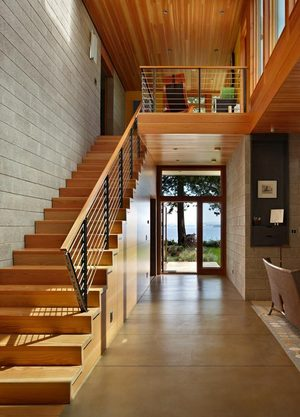 """A two-story CMU (concrete masonry unit) wall runs across the home. """"This grounding element not only provides a threshold separation between public and private, it also is the main heat sink to help stabilize temperatures and reduce the heat swings,"""" says architect Matthew Coates. """"This central gallery is the main vertical access for the home. It helps ground the whole construct."""""""