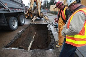 A Seattle Public Utilities crew goes to work after a valve on a water main broke Wednesday on South Juneau Street at Martin Luther King Jr. Way South. As many as 1,300 customers lost water service before it was restored.