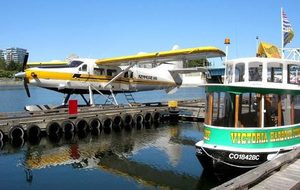 A Kenmore Air floatplane awaits at a dock in Victoria's Inner Harbour by one of the city's mini passenger ferries.