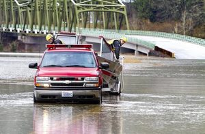 Eastside Fire and Rescue test out their rescue boat along the closed Northeast Tolt Hill Road in Carnation as flood waters rise along the Snoqualmie River on Wednesday morning. This route which connects Carnation with Redmond is closed until flood waters go down.