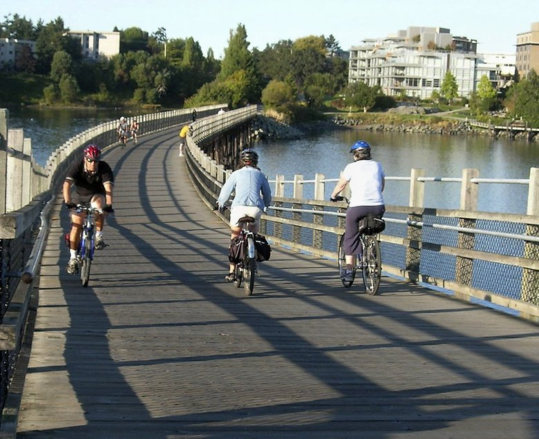 Bicyclists cross Victoria's Selkirk Trestle Bridge on the Galloping Goose trail, a former railway line.  (Kristin Jackson / The Seattle Times)