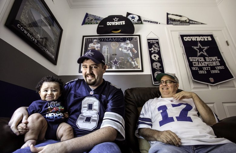 """Geramy Slayton, left, sits with his son, Grant, and friend David Krause, right, in Slayton's Seattle """"man cave"""" devoted to the Dallas Cowboys."""