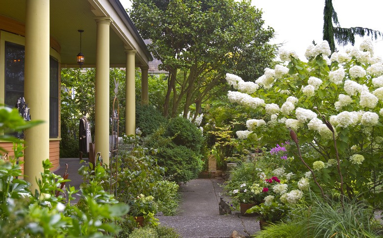 The front porch of Lynda Bazan's castle-home is larger than the house she sold in order to buy it. She and son Micah have restored the gardens, planting ornamentals, vegetables and fruit along the front of the house.