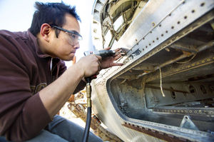 Kevin Tanamas works with a drill to remove a rivet in a DC-9 Swiss Air fuselage during an airframe and power-plant program class at Orange Coast College in Costa Mesa, Calif.