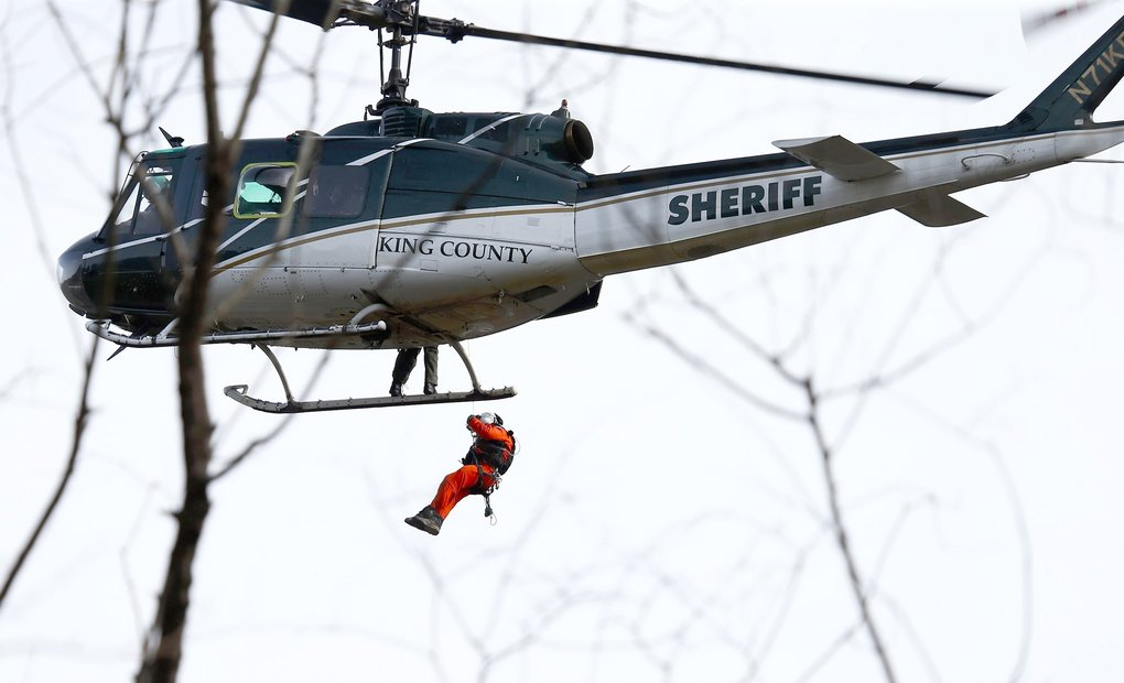 A King County Sheriff helicopter circles the scene as a rescue worker begins to lower himself down on a line at the mudslide near mile marker 37, on Monday, March 24, 2014.