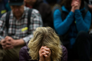 "Residents bow their head in prayer as they attend a prayer service dedicated to the communities affected by the Highway 530 mudslide, during the ""Together Evening of Prayer"" at Haller Middle School in Arlington, on Friday, April 4, 2014."