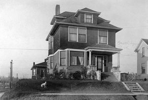 THEN: When it was built in 1902, this box home, with classic Ionic pillars at the porch, was set above the northwest corner of the freshly graded Brooklyn Avenue and Northeast 47th Street in the University District.