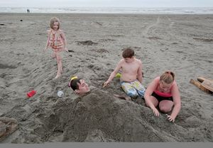 Haden Smith   lets his siblings and cousin bury him in sand at Ocean Shores.  Riley Smith,  left, looks on as her brother Tristin Smith and her cousin Dakota Hendrickson add more sand. The Smiths are from Bremerton. Dakota was visiting from Texas.