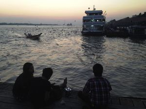 Teens spend a Saturday night watching the ferry and other boats at the harbor in Yangon, Myanmar.