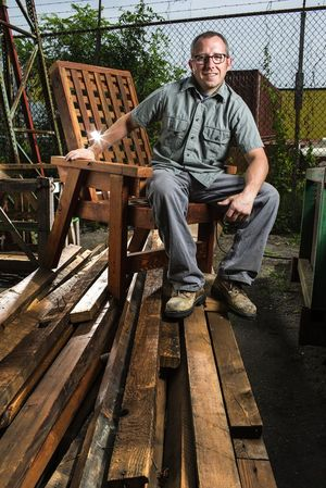 Joel Blaschke, co-owner of Ballard Reuse, shows off a lounge chair made from salvaged fir and crafted by fellow Ballard Reuse staffer James Taylor. Blaschke is sitting atop a pile of salvaged fir.
