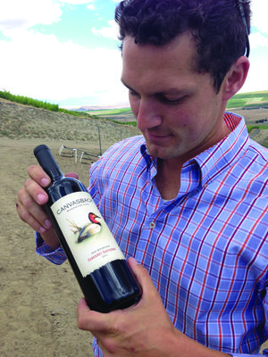 Winemaker Brian Rudin holds a bottle of the Canvasback 2012 cabernet sauvignon at the winery's newly planted vineyard on Red Mountain. Canvasback is owned by Duckhorn, one of the most famous wineries in California.