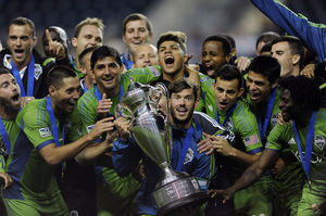 Sounders FC midfielder Brad Evans holds the championship trophy and celebrates with teammates after Seattle's 3-1 overtime win over Philadelphia in the U.S. Open Cup final.
