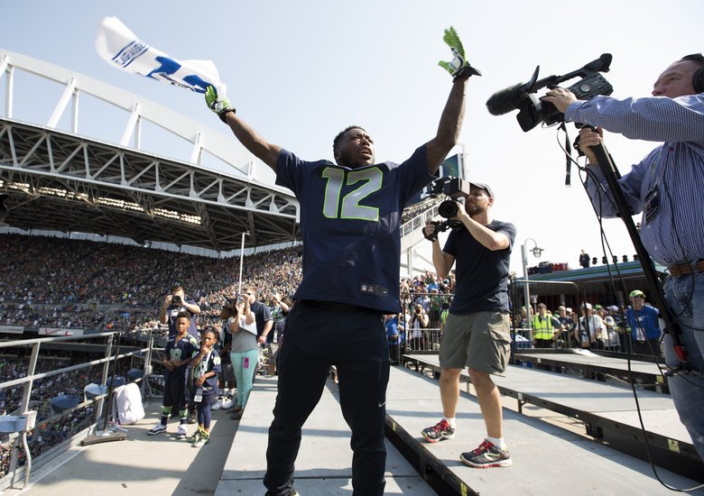 Nate Robinson raises the 12th Man flag before the Seattle Seahawks play the Denver Broncos at CenturyLink Field in 2014.