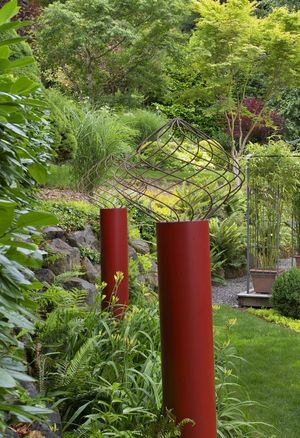 Bard fashioned red columns out of painted PVC pipe and topped them with a swirl of rebar cages to liven up the narrow back garden.